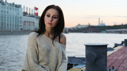 Young woman with serious expression sitting on pier