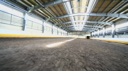 Empty indoor horse riding hangar with ground covering