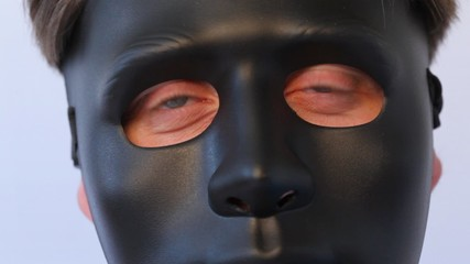 man in black mask on face turns in profile close up