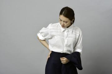 アジアの若い女性会社員 腰痛