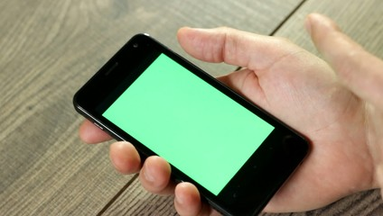hand with a smartphone with green screen