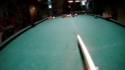 Man begins game on billiards striking by cue on billiard balls