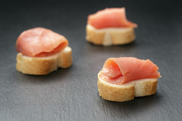 baguette slices with curred salmon on slate background