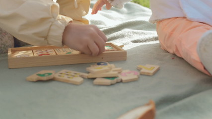 Little girl with a baby playing with wooden educational toy on