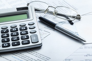 Tax. Calculating numbers for income tax return with pen and