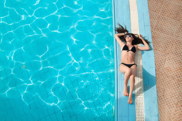 beautiful young woman relaxing in the swimming pool. View from a
