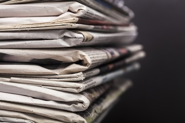 Journalism. Stack of newspapers on black background