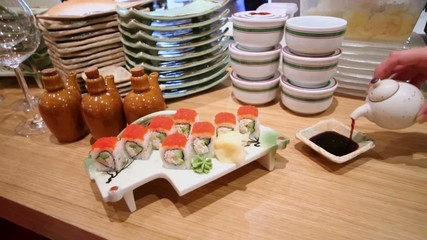 Hand pours sauce to plate on table with rolls at dish