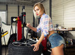 girl mechanic replace tires on wheels - 80146375