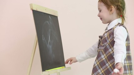 Little girl plays by yellow pointer and draws at chalkboard