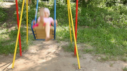 girl in dress and hat shakes on color children swing