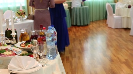 women near table in restaurant decorated for wedding celebration