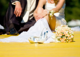wedding shoes and rose bouquet of bride and couple in blur