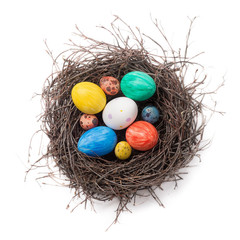 Colorful Easter eggs in a nest on a white background. Top view