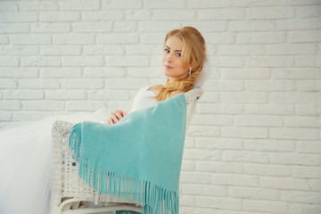 Blonde pretty bride on chair with blue wrap. Soft, vanilla color