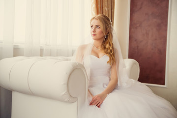 Beautiful bride on chair near window in the interior of a large,