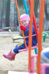Little girl sitting on playgrounds swing