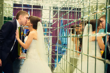 Young wedding couple kissing in room with mirrors