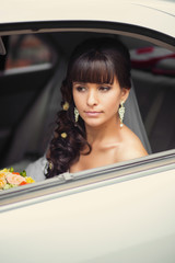 close-up portrait of a pretty bride in a car window