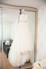 wedding dress hanging on mirror at hotel room