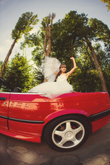 Runaway bride. Beautiful woman on red cabriolet