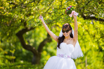 Beautiful bride in sunglasses posing in park
