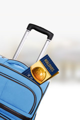 Maldives. Blue suitcase with guidebook.