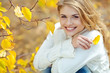 Portrait of beautiful young woman walking outdoors in autumn  - 80150566