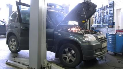 Mechanics repair car in garage of car-care center