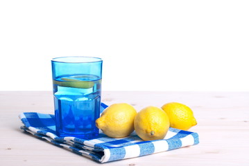 water with lemon and mint in blue glass on the table side view o