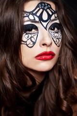 portrait of pretty brunette woman with  face art