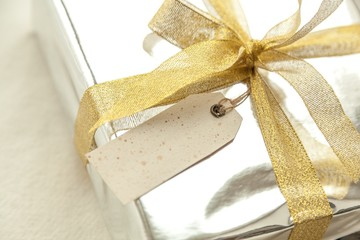 Gift. Gold Christmas gift box with blank paper label and