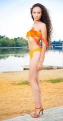 Sexy woman standing in bikini on beach