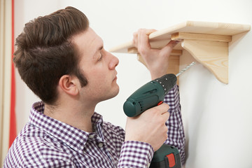 Man Putting Up Wooden Shelf At Home Using Electric Cordless Dril