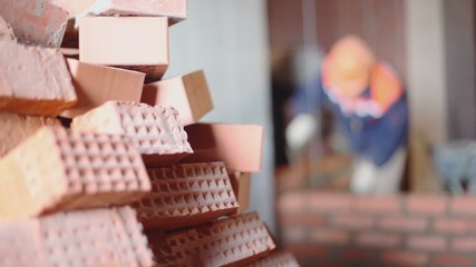 Pile of bricks at background of few workers build wall unfocused