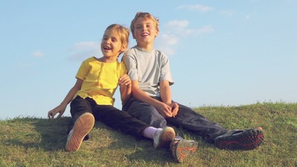 Two kids boy with little girl sing song and sway on grass hill at sunny summer day