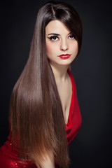 Beautiful woman with long brown straight hairs and red dress