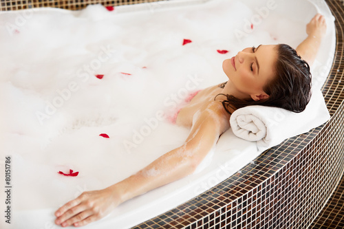 Woman Relaxing in Bubble Bath With Rose Petals. Body Care
