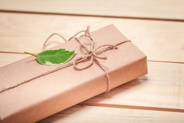 Birthday. gift package wrapped with paper and rope with a leaf