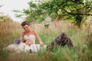 Невеста обнимает жениха,лежащего на траве