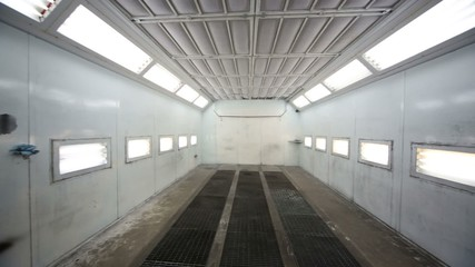 Inside paint-spraying booth with metal walls for cars
