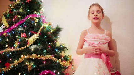 Little girl in pink dress with ribbon near christmas tree