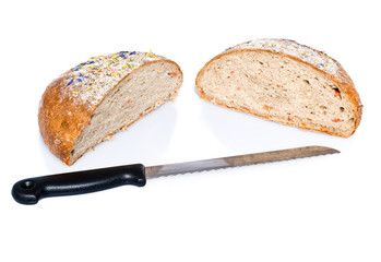 Two half loafs of bread with knife