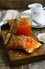 Breakfast with rye bread, apricot jam, sunflower seeds and milk