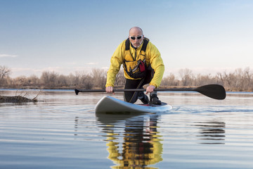 Senior male on stand up paddling (SUP) board