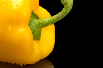 Cut shot of yellow bell pepper isolated on black with water drop