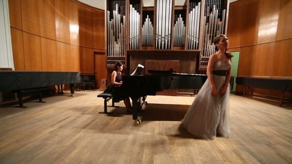 Review opera stage with woman pianist playing piano and singer