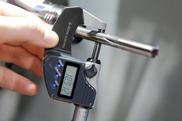 Industrial worker measure detail with digital caliper micrometer