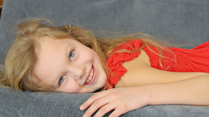 Blonde girl lying on the sofa and smiling into the camera