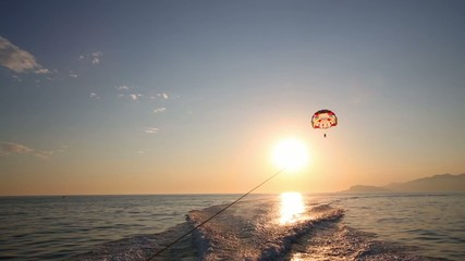 Glider flies over sea at sunny summer evening and traces of boat